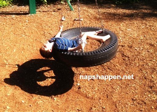 child asleep in tire swing