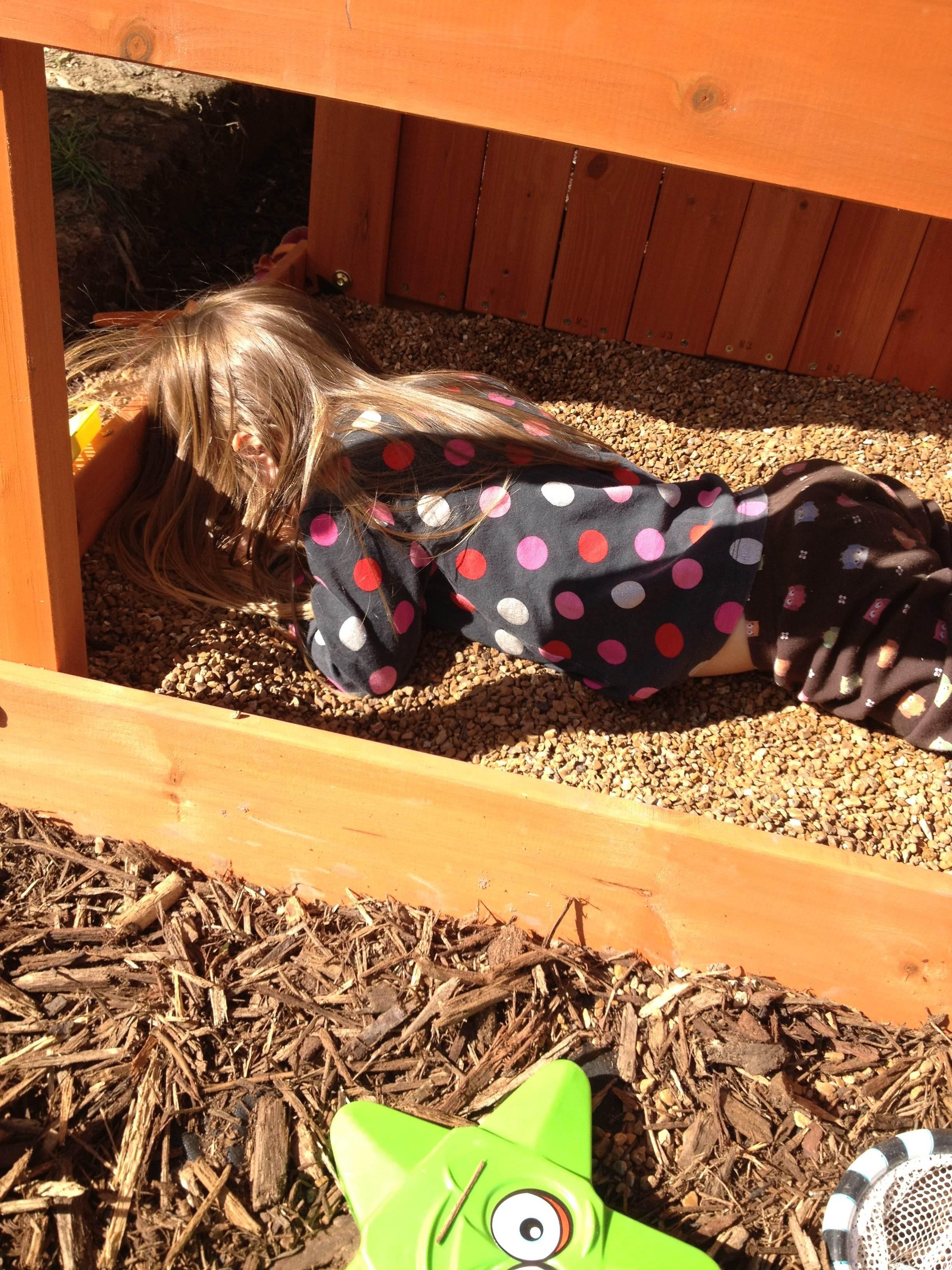 Child asleep in sandbox